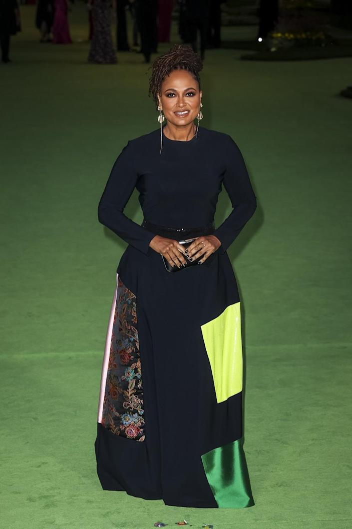 A woman posing in a patterned, black dress on a green carpet