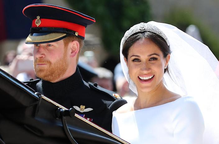 TOPSHOT - Britain's Prince Harry, Duke of Sussex and his wife Meghan, Duchess of Sussex begin their carriage procession in the Ascot Landau Carriage after their wedding ceremony at St George's Chapel, Windsor Castle, in Windsor, on May 19, 2018. (Photo by Gareth Fuller / POOL / AFP) (Photo credit should read GARETH FULLER/AFP via Getty Images)