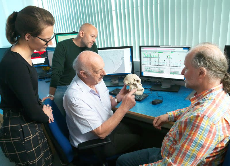 Ron Clarke displays a replica of a fossil skull of Little Foot next to Amwlie Beaudet, Dominic Stratford, and Robert Atwood at the lab in Oxford