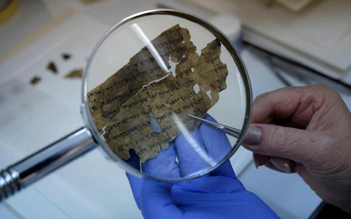 A worker of the Israeli Antiquity Authority sews fragments of the Dead Sea scrolls which includes biblical verses in a preservation laboratory of the Israel Museum in Jerusalem - Moment Mobile ED