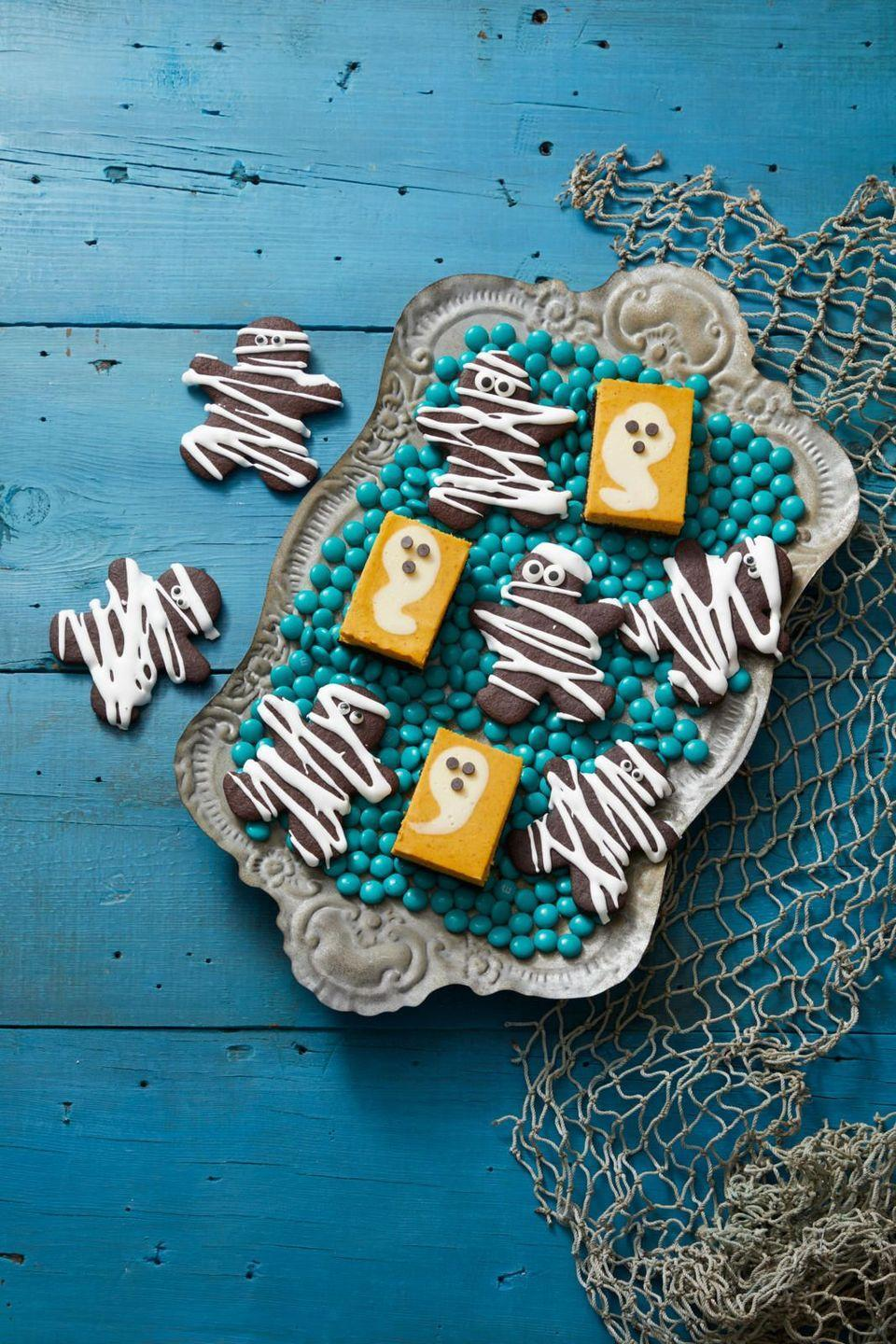 """<p>For a fork-free dessert, you can't go wrong with these pumpkin cheesecake bars. And they get extra festive with the addition of some ghost-shaped cream cheese filling.</p><p><em><strong><a href=""""https://www.womansday.com/food-recipes/a33562053/pumpkin-cheesecake-ghosts-recipe/"""" rel=""""nofollow noopener"""" target=""""_blank"""" data-ylk=""""slk:Get the Pumpkin Cheesecake Ghosts recipe."""" class=""""link rapid-noclick-resp"""">Get the Pumpkin Cheesecake Ghosts recipe. </a></strong></em></p>"""