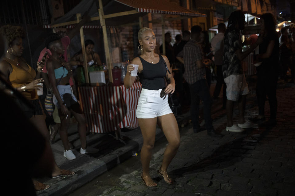 A woman dances during a street performance by the Brazilian band Atitude Nossa as the restrictions related to the COVID-19 pandemic are eased in Rio de Janeiro, Brazil, Monday, Oct. 5, 2020. Since the beginning of October, live shows are now permitted in Rio de Janeiro. (AP Photo/Silvia Izquierdo)