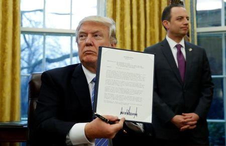 U.S. President Donald Trump holds up the executive order on the reinstatement of the Mexico City Policy after signing in the Oval Office of the White House in Washington January 23, 2017. At his side is White House Chief of Staff Reince Priebus.  REUTERS/Kevin Lamarque