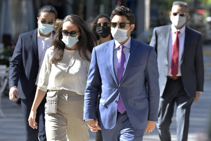 Former Fall River, Mass. Mayor Jasiel Correia, right, and his wife Jenny Fernandes, left, arrive for a court appearance at the John Joseph Moakley United States Courthouse, Monday, Sept. 20, 2021, in Boston. Correia, who was elected at the age of 23 with promises to rejuvenate the struggling mill city, was scheduled to be sentenced for stealing from investors in a smartphone app he created and extorting hundreds of thousands of dollars in bribes from marijuana businesses. (AP Photo/Josh Reynolds)