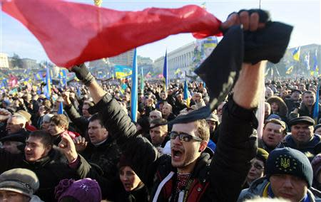 Pro-European integration protesters shout slogans and wave flags during a rally in Independence square in Kiev December 22, 2013. REUTERS/Gleb Garanich