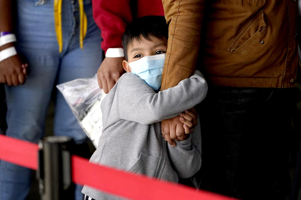 A migrant child holds onto a woman's arm as they wait to be processed by a humanitarian group after being released from U.S. Customs and Border Protection custody at a bus station, Wednesday, March 17, 2021, in Brownsville, Texas. Team Brownsville, a humanitarian group, is helping migrants seeking asylum with clothing and food as well as transportation to the migrant's final destination in the U.S. (AP Photo/Julio Cortez)