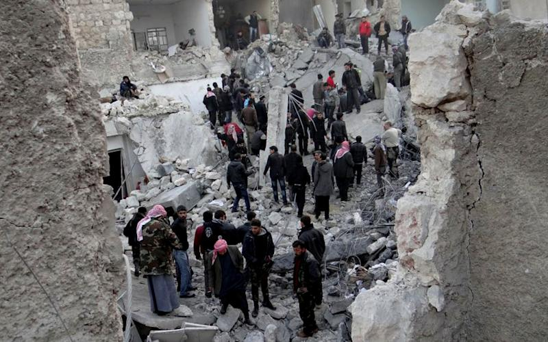 In this citizen journalism image taken on Monday, Jan. 14, 2013, provided by Aleppo Media Center AMC which has been authenticated based on its contents and other AP reporting, people gather around destroyed buildings after airstrikes that targeted Aleppo, Syria. (AP Photo/Aleppo Media Center AMC)