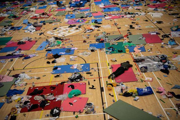 PHOTO: A man sleeps in a gym that is strewn with abandoned belongings at Hong Kong Polytechnic University, which has been taken over by anti-government protesters, on Nov. 21, 2019, in Hong Kong. (Laurel Chor/Getty Images)