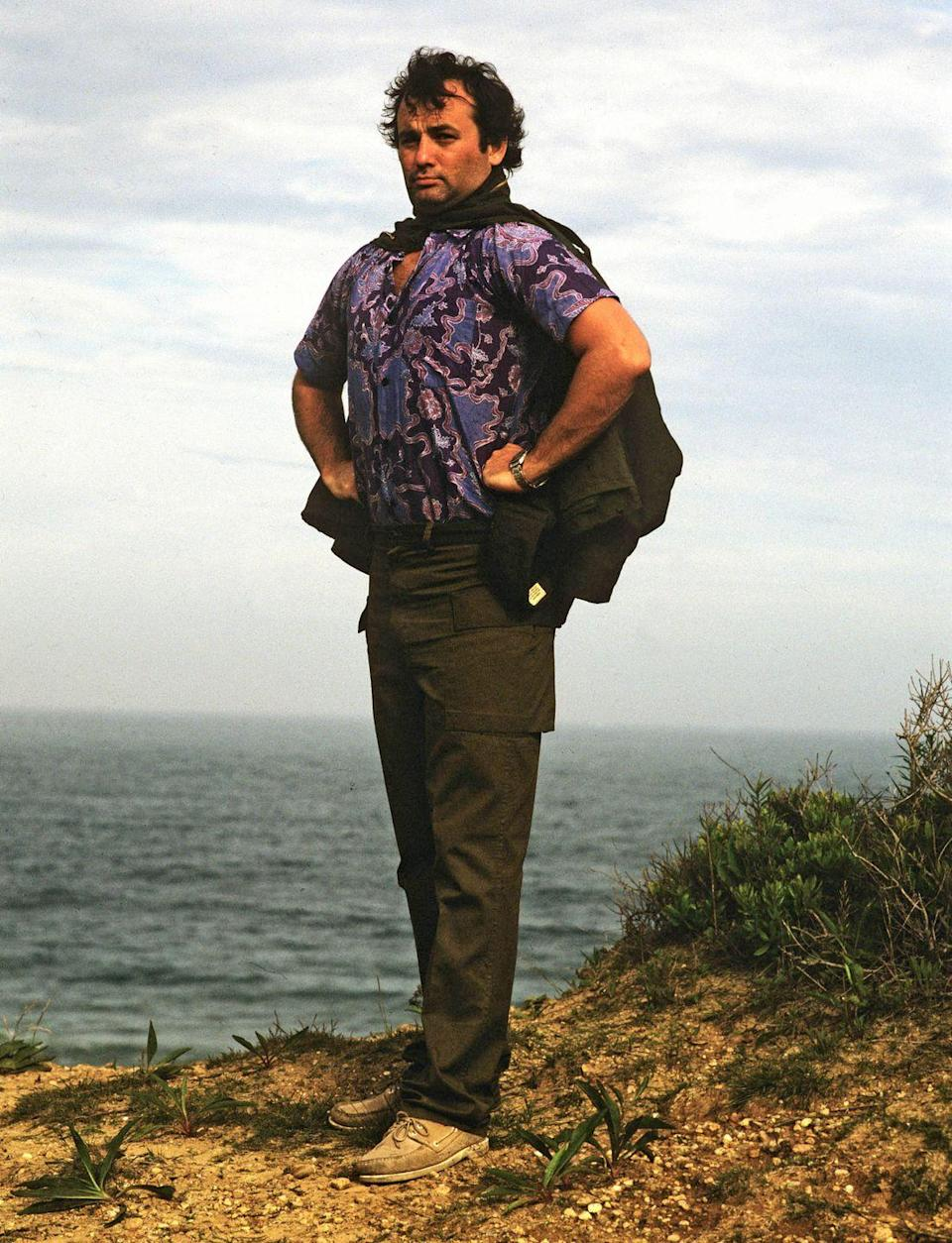 <p>Portrait of Bill Murray as he stands, hands on his hips, on a sea-side cliff-edge during a photoshoot for Rolling Stone magazine, 1981.</p>