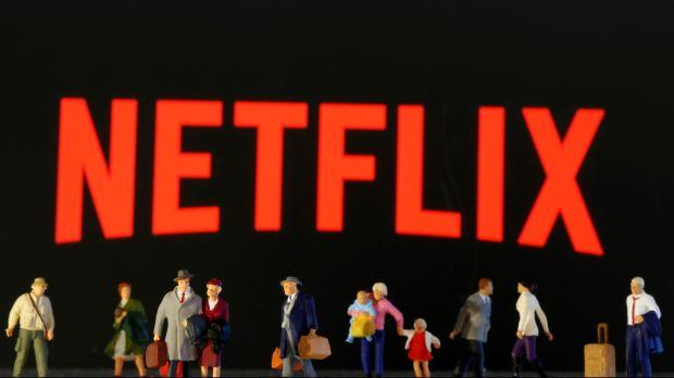 Small toy figures are seen in front of diplayed Netflix logo