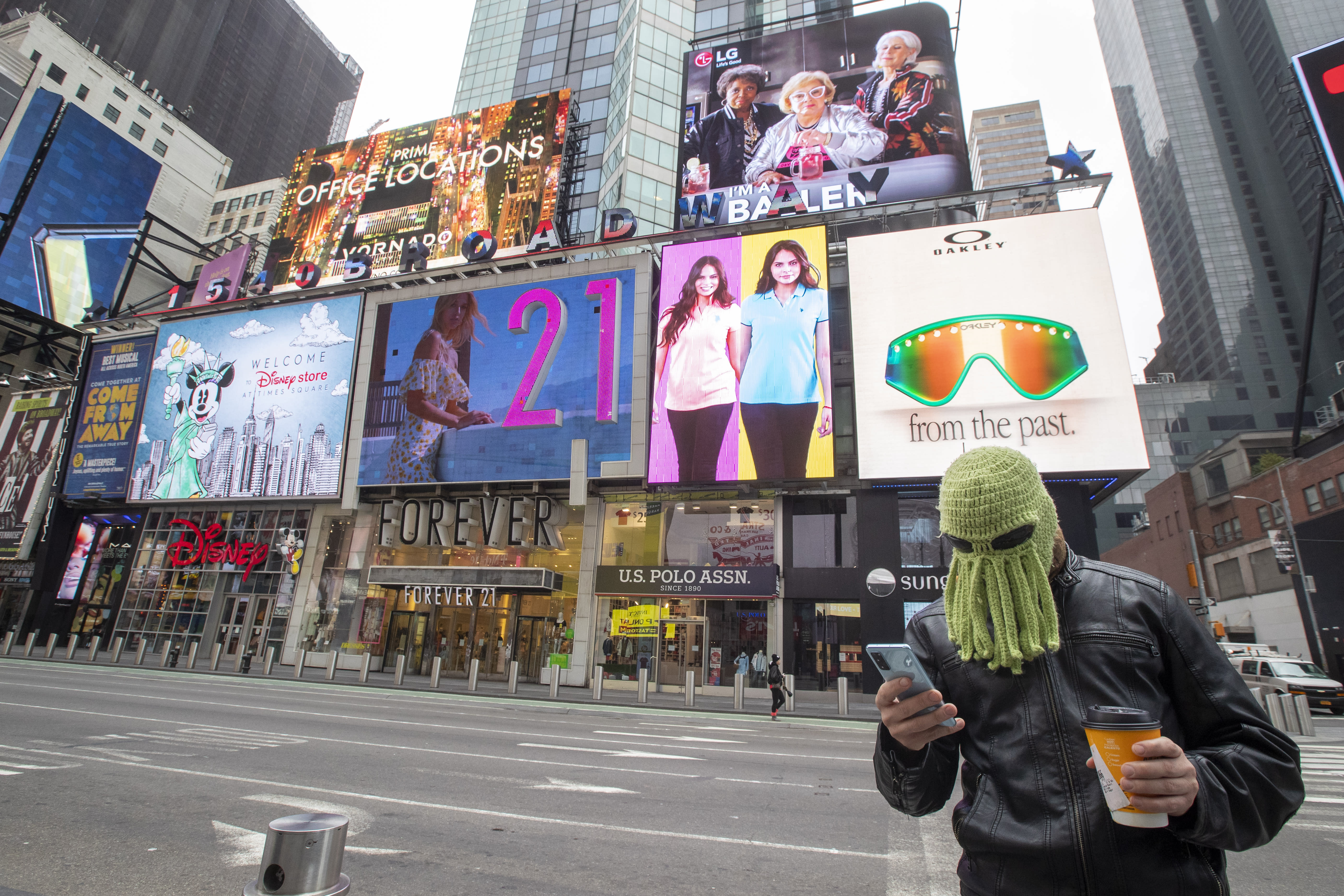 Jon Makay, of Harlem, wears an octopus hat to fend off coronavirus, Wednesday, March 25, 2020, in New York's Times Square. The number of people hospitalized with COVID-19 in New York climbed to 3,800, with close to 900 in intensive care, with the peak of the outbreak weeks away, Gov. Andrew Cuomo said Wednesday. The new coronavirus causes mild or moderate symptoms for most people, but for some, especially older adults and people with existing health problems, it can cause more severe illness or death. (AP Photo/Mary Altaffer)
