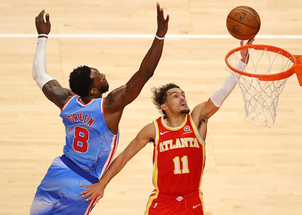 Trae Young attacks the basket against Jeff Green during overtime.