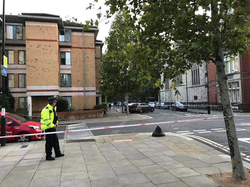 Police officers stand at the cordon of the stabbing in Camden