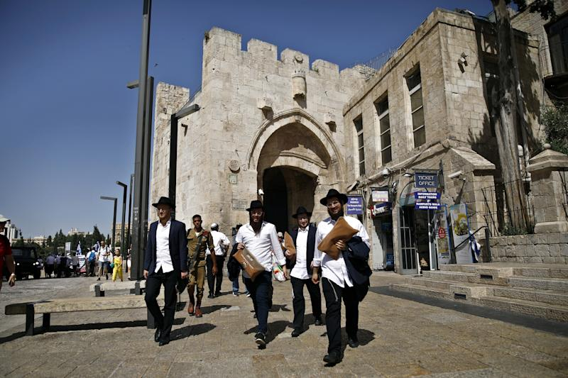 Ultra-Orthodox Jewish men carry bags as they walk near Jaffa Gate in Jerusalem's Old City. (Photo: Nir Elias/Reuters)