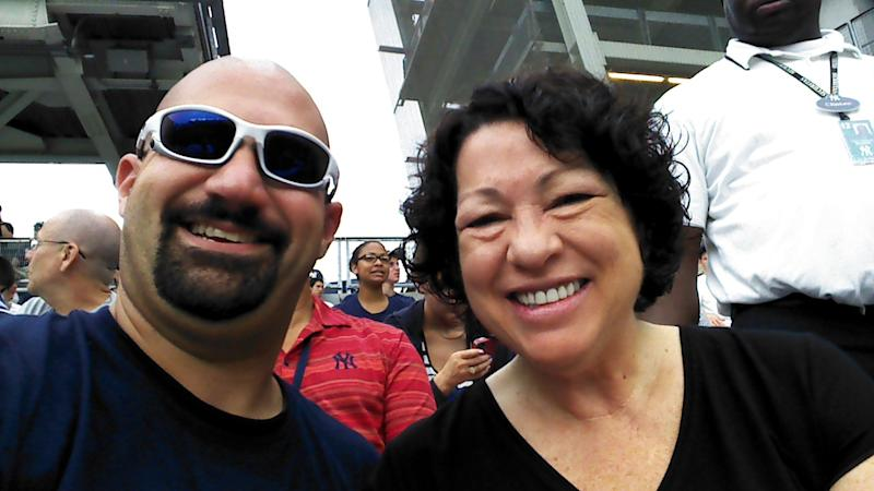 """In this cell phone image provided by """"Bald Vinny"""" Milano, Supreme Court justice and Bronx native Sonia Sotomayor, right, and Milano smile for a photo during a baseball game between the New York Yankees and Baltimore Orioles, Wednesday, Aug. 1, 2012 at Yankee Stadium in New York. Sotomayor sat in Section 203 of the right-field stands for the first-inning """"Roll Call"""" of New York's starting lineup. (AP Photo/""""Bald Vinny"""" Milano)"""