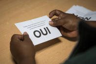 A volunteer holds a Yes vote for independence as she counts ballots in a voting station of Noumea, New Caledonia, Sunday, Oct.4, 2020. Voters in New Caledonia, a French archipelago in the South Pacific, were deciding Sunday whether they want independence from France in a referendum that marks a milestone in a three-decade decolonization effort. If voters choose independence, a transition period will immediately open so that the archipelago can get ready for its future status. Otherwise, New Caledonia will remain a French territory. (AP Photo/Mathurin Derel)