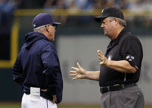 Second base umpire Joe West gestures as he talks to Tampa Bay Rays manager Joe Maddon, left, during the sixth inning of a baseball game against the Toronto Blue Jays Wednesday, May 23, 2012, in St. Petersburg, Fla. West ruled Rays second baseman Will Rhymes missed second base on a play involving Toronto's Edwin Encarnacion. (AP Photo/Chris O'Meara)