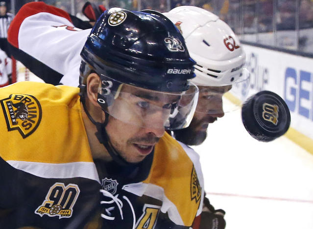 Boston Bruins center Chris Kelly, left, and Ottawa Senators defenseman Eric Gryba (62) battle for the puck along the boards during the second period of an NHL hockey game in Boston, Saturday, Feb. 8, 2014. (AP Photo/Elise Amendola)