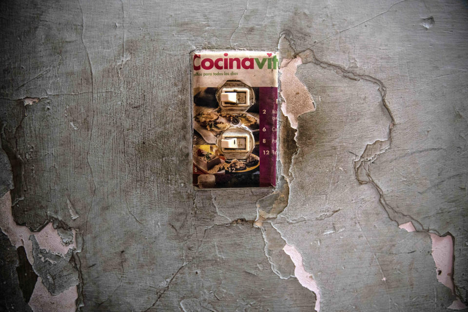 """A makeshift light switch plate is decorated with an image of baked goods in the home of Yuliet Colon, a 39-year-old mother of two and a contributor to the Facebook page, """"Recipes from the Heart,"""" in Havana, Cuba, Friday, April 2, 2021. (AP Photo/Ramon Espinosa)"""