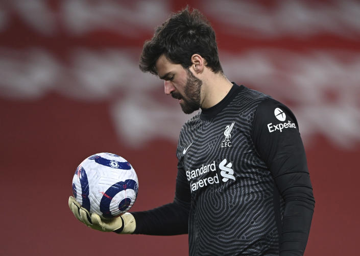 Liverpool's goalkeeper Alisson looks down at the ball during the English Premier League soccer match between Liverpool and Everton at Anfield in Liverpool, England, Saturday, Feb. 20, 2021. Everton won the game 2-0. (Lawrence Griffiths/ Pool via AP)