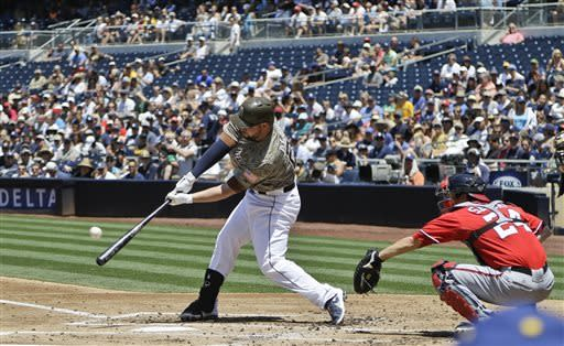 San Diego Padres' Yonder Alonso drives a deep sacrifice fly to right that brings in a run during the Padres three run first inning against the Washington Nationals in the MLB National League baseball game in San Diego Sunday, May 19, 2013. (AP Photo/Lenny Ignelzi)