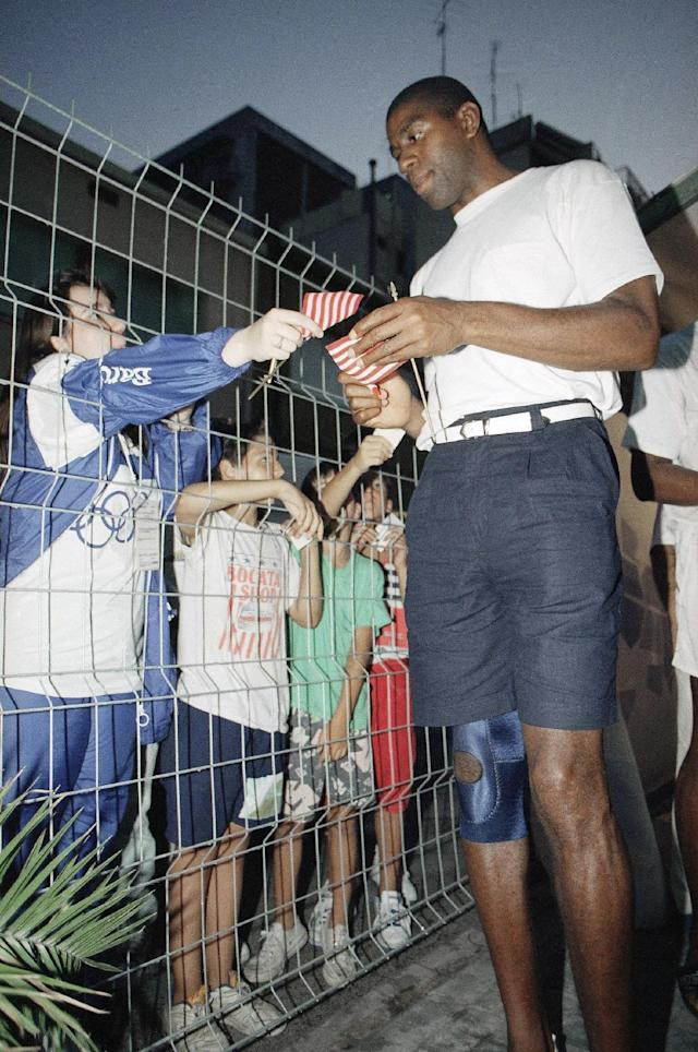 FILE - In this July 28, 1992, file photo, U.S. Olympic basketball player Magic Johnson wears a knee brace as he signs autographs for local children in Barcelona, Spain. Johnson injured his knee during an Olympic game Monday against Croatia. (AP Photo/Bill Sikes, File)