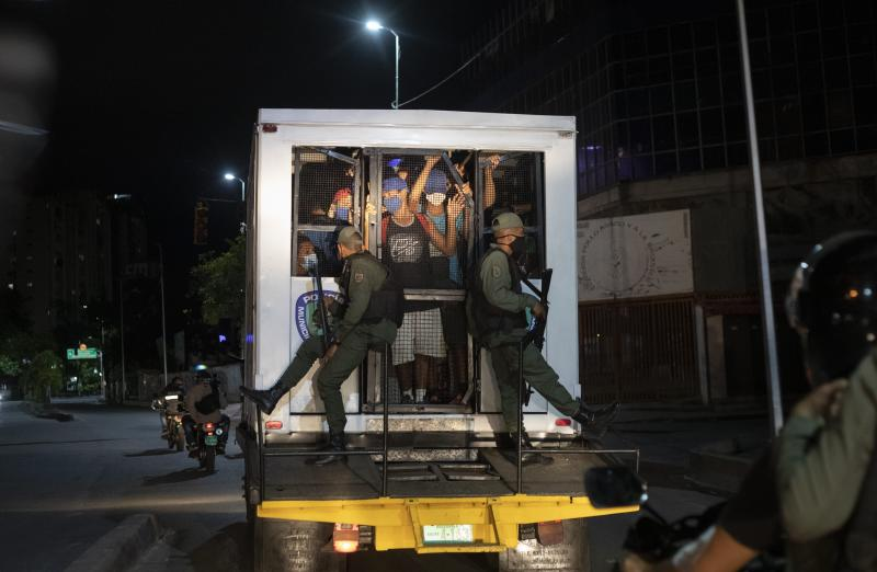 Men who were detained for not complying with COVID-19 regulations by breaking curfew or attending block parties, are transported in a police van to a coliseum, in the Petare neighborhood of Caracas, Venezuela, early Saturday, Aug. 8, 2020, as part of an operation to educate residents on the risks of being out and socializing in groups amid the new coronavirus pandemic. Residents are released a few hours later after receiving instruction on best social distancing practices. (AP Photo/Ariana Cubillos)