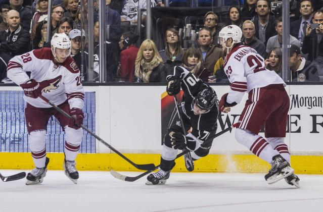 Los Angeles Kings forward Tanner Pearson (70) falls to the ice between Phoenix Coyotes forward Lauri Korpikoski (28) and defenseman Oliver Ekman-Larsson (23) during the second period of an NHL hockey game, Wednesday, April 2, 2014, in Los Angeles. (AP Photo/Ringo H.W. Chiu)