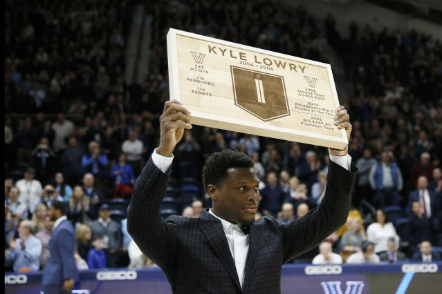 Kyle Lowry, a former Villanova player and current Toronto Raptors player, holds up a plaque during a ceremony honoring him during halftime of an NCAA college basketball game between Villanova and St. John's, Wednesday, Feb. 26, 2020, in Villanova, Pa. (AP Photo/Matt Slocum)