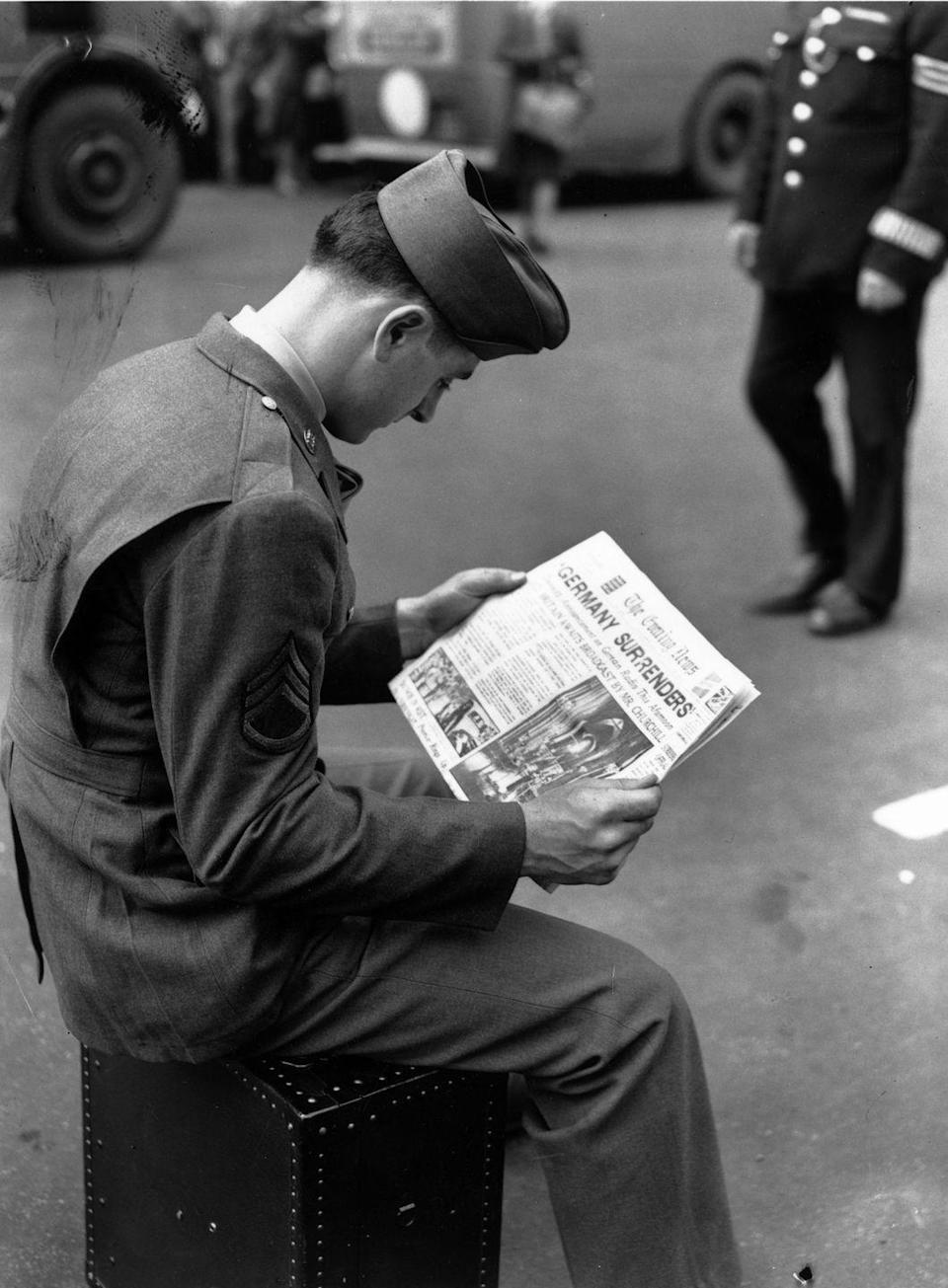 """<p>While stationed in London, England an American solider sits down to read the day's paper headlined, """"Germany Surrenders.""""</p>"""