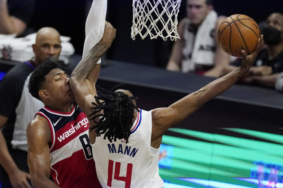 Los Angeles Clippers guard Terance Mann, right, elbows Washington Wizards forward Rui Hachimura on the face as he shoots during the second half of an NBA basketball game Tuesday, Feb. 23, 2021, in Los Angeles. The Clippers won 135-116. (AP Photo/Mark J. Terrill)