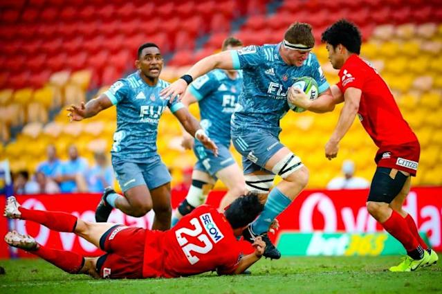 Canterbury Crusaders' Tom Sanders is tackled by Japan Sunwolves' Shogo Nakano and Keisuke Moriya (right) in front of a sparse crowd at Brisbane on Saturday, hours before the Super Rugby season was suspended (AFP Photo/Patrick HAMILTON)