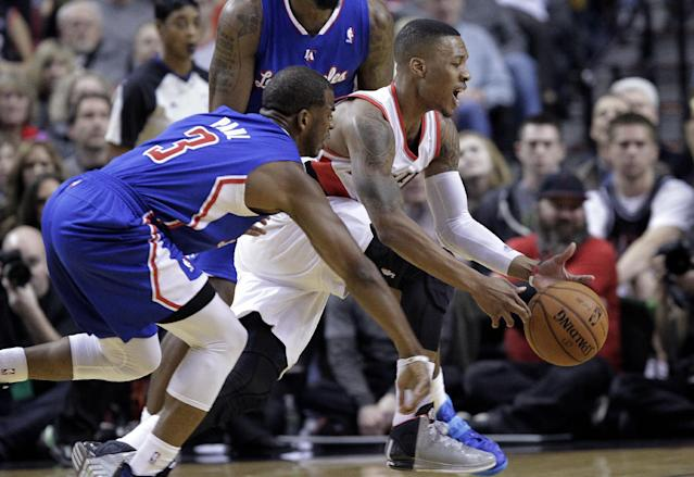 Portland Trail Blazers guard Damian Lillard, right, loses control of the ball as Los Angeles Clippers guard Chris Paul defends during the first half of an NBA basketball game in Portland, Ore., Thursday, Dec. 26, 2013. (AP Photo/Don Ryan)