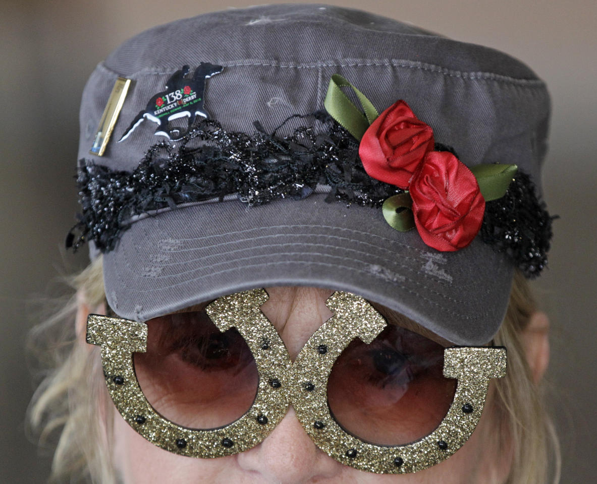 Sandy Cousins, of Fond du Lac, Wis., wears horseshoe glasses while waiting for the 138th Kentucky Derby horse race at Churchill Downs, Saturday, May 5, 2012, in Louisville, Ky. The Run for the Roses draws them to Churchill Downs. But what race goers wear is as much a spectacle in itself. (AP Photo/Mark Humphrey)