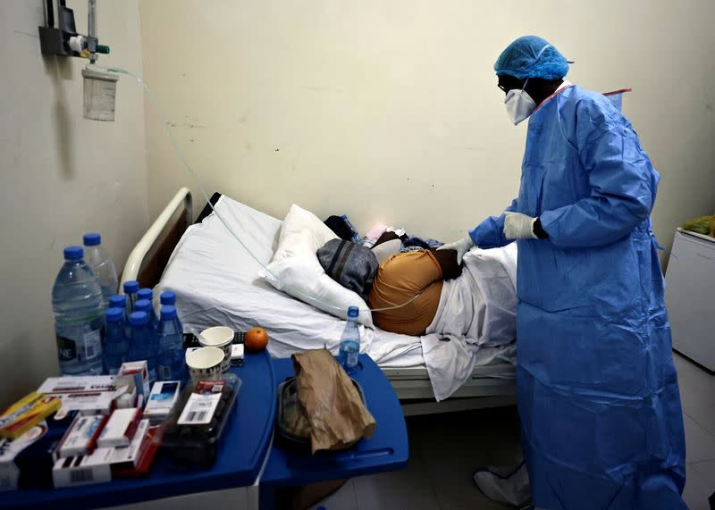Professor Moussa Seydi, wearing his personal protective equipment (PPE) talks to a patient, who is suffering from the coronavirus disease (COVID-19) at the infectious diseases department of the University Hospital Fann, in Dakar