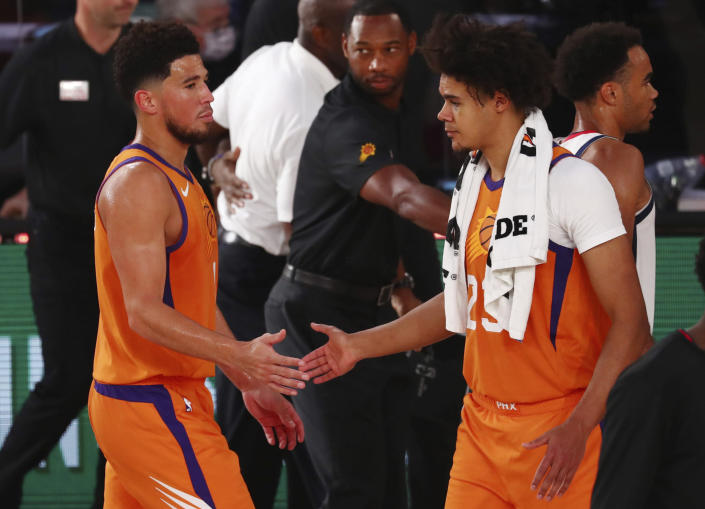 Phoenix Suns guard Devin Booker (1) slaps hands with forward Cameron Johnson (23) after defeating the Washington Wizards in an NBA basketball game in Lake Buena Vista, Fla., Friday, July 31, 2020. (Kim Klement/Pool Photo via AP)