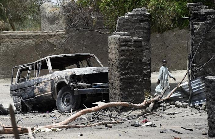 A boy walks past a burnt house and car on April 6, 2015 in N'Gouboua, near Lake Chad, which was attacked by Islamist group Boko Haram (AFP Photo/Philippe Desmazes)