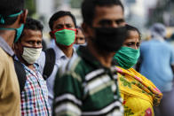 Commuters wearing face masks as a precautionary measure against the coronavirus wait for a bus in Kolkata, India, Saturday, Oct. 10, 2020. India's total coronavirus positive cases near 7 million with another 73,272 infections reported in the past 24 hours. The Health Ministry on Saturday put the total positive caseload at 6.97 million, second to 7.66 million infections registered in the worst-hit United States. (AP Photo/Bikas Das)