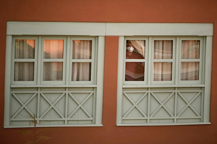 A man looks out the window at a quarantine hotel on the Canary Island of Tenerife, Spain, February 26.
