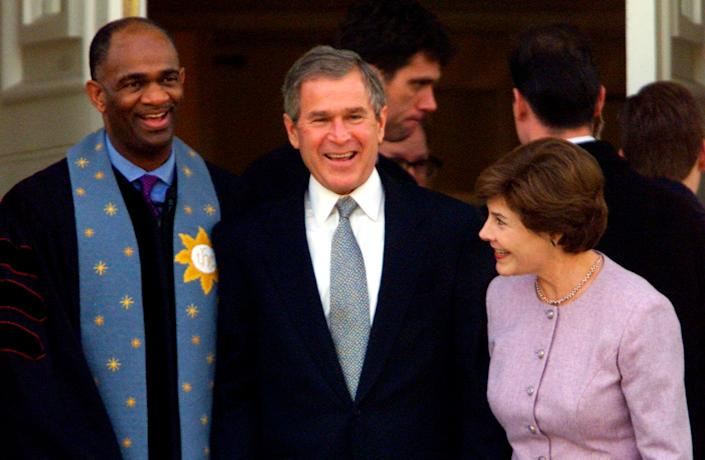 George W. Bush stands with his wife Laura andRev. Kirbyjon H. Caldwell after services at Tarrytown United Methodist Church in Austin, Texas, onDec. 14, 2000. Caldwellhas long been a spiritualadviser to Bush. (Photo: Reuters Photographer / Reuters)