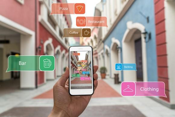 """Looking at a smart phone whilst walking down a narrow street. The buildings are tagged with augmented reality labels like """"coffee"""" and """"bar"""", telling the user what they are."""