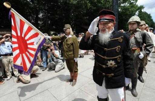 A war veteran (2nd R) leads others clad in costumes of the Imperial Japanese Army during a visit to Yasukuni Shrine to pray for war victims in Tokyo on August 15, 2012