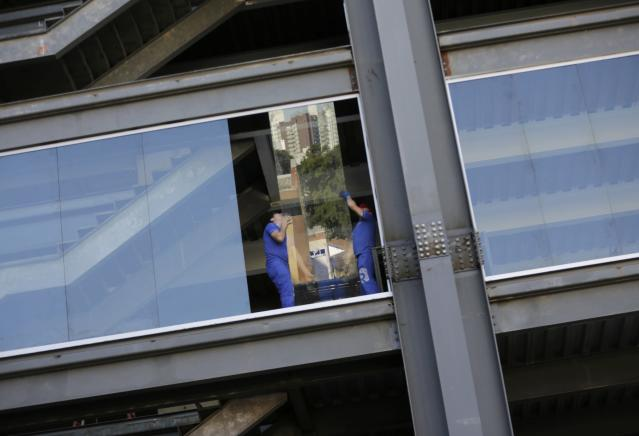 Construction workers install glass at the Arena Baixada soccer stadium in Curitiba June 13, 2014. The stadium will host the first of four 2014 World Cup matches on June 16. REUTERS/Henry Romero (BRAZIL - Tags: BUSINESS CONSTRUCTION SOCCER SPORT WORLD CUP)