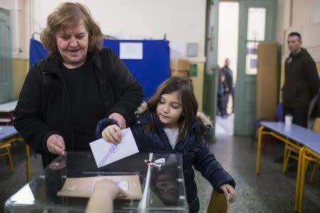A woman with a child casts her ballot at a polling station in an elementary school during Greece's parliamentary elections in Athens January 25, 2015. REUTERS/Marko Djurica