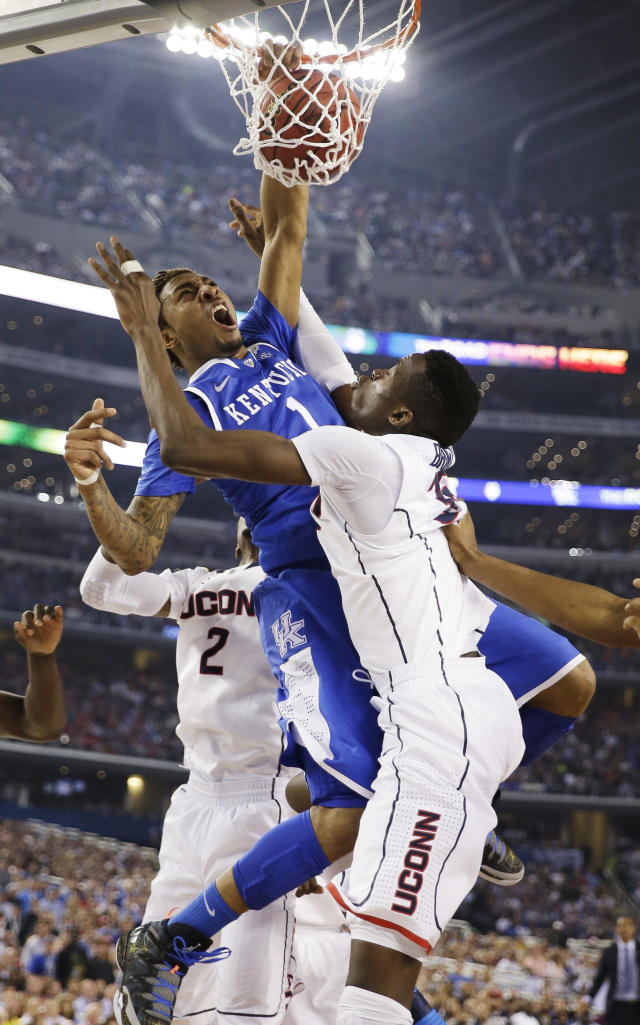 Kentucky guard James Young (1) dunks between Connecticut forward DeAndre Daniels (2) and center Amida Brimah (35) during the second half of the NCAA Final Four tournament college basketball championship game Monday, April 7, 2014, in Arlington, Texas. (AP Photo/David J. Phillip)