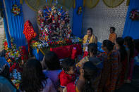 Devotees offer prayers during Durga Puja festival in Gauhati, India, Saturday, Oct. 24, 2020. Weeks after India fully opened up from a harsh lockdown and began to modestly turn a corner by cutting new infections by near half, a Hindu festival season is raising fears that the disease could spoil the hard-won gains. Health experts worry the festivals can set off a whole new cascade of infections, further testing and straining India's battered health care system. (AP Photo/Anupam Nath)