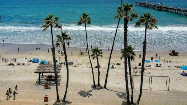 PHOTO: Beachgoers take to the water on a warm summer day at the San Clemente Pier in San Clemente, Calif., June 30, 2020. (Allen J. Schaben/Los Angeles Times via Shutterstock)