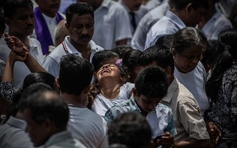 A woman cries as a coffin is buried during a mass burial near St Sebastian Church on April 23, 2019 in Negombo, Sri Lanka - Credit: Getty