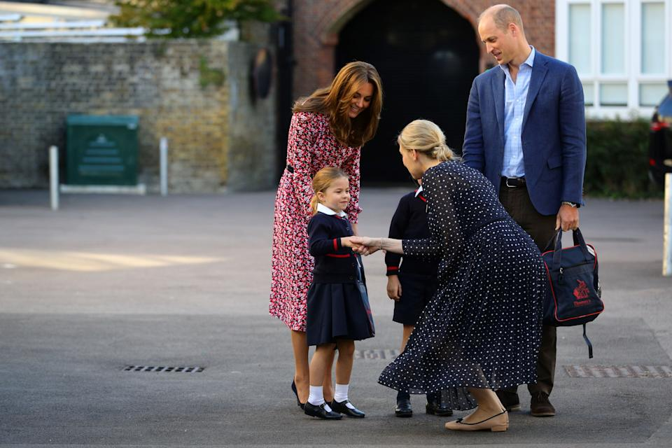 Britain's Princess Charlotte of Cambridge, accompanied by her father, Britain's Prince William, Duke of Cambridge, her mother, Britain's Catherine, Duchess of Cambridge, is greeted by Helen Haslem, head of the lower school (CR) on her arrival for her first day of school at Thomas's Battersea in London on September 5, 2019. (Photo by Aaron Chown / POOL / AFP)        (Photo credit should read AARON CHOWN/AFP/Getty Images)