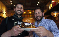 """In this May 8, 2019 photo, Lou Liapis, left, and brother Pete Liapis hold the """"Gyro Step"""" at their restaurant Georgie Porgie's in Oak Creek, Wis. They created the Greek-inspired sandwich, which includes a burger patty, gyro meat, feta cheese and tzatziki sauce, in honor of the fancy footwork of Bucks star Giannis Antetokuonmpo, who was born in Greece. It will be available during the playoffs. (AP Photo/Carrie Antlfinger)"""